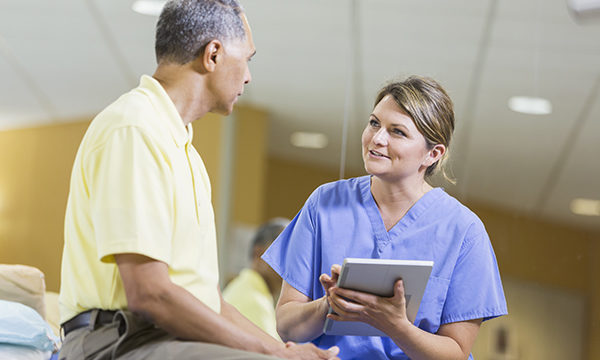 A nurse with a tablet handset talking to a patient