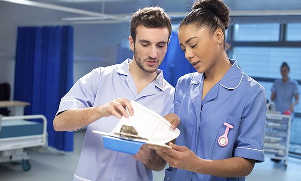 Two nurses looking at notes on a piece of paper
