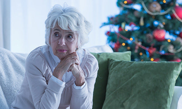 Older woman looking unhappy in room with Christmas decorations