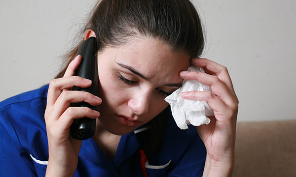 Nurse talking on the phone and looking stressed