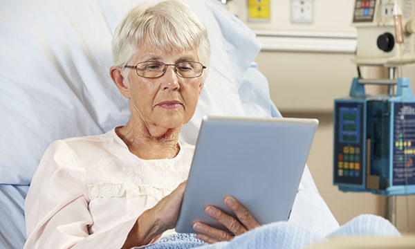 Hospital patient in bed looking at iPad