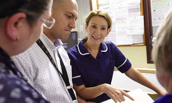 nurse talks to team colleagues