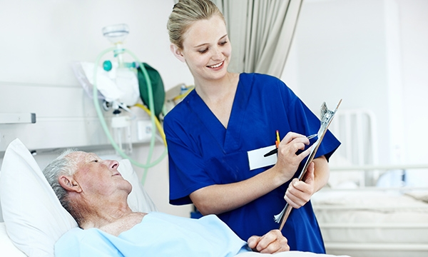 A nurse with a clipboard talks to an elderly patient in a hospital bed