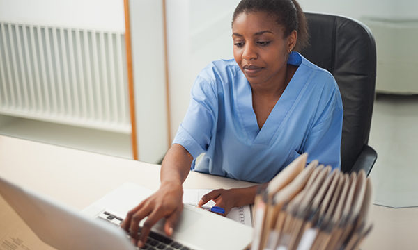 A nurse typing on a computer keyboard