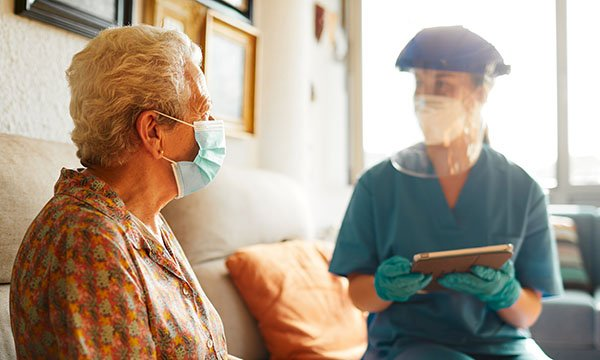 A nurse in PPE talking to an elder lady with a face mask. Approximately 27% of US COVID-19 deaths have been nursing home residents. Picture: iStock