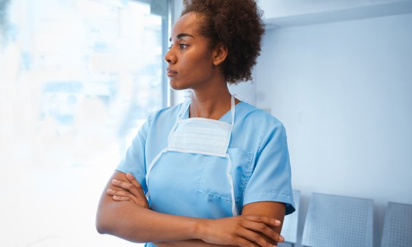 A woman in scrubs standing in a clinical area, reflecting on her experiences at work